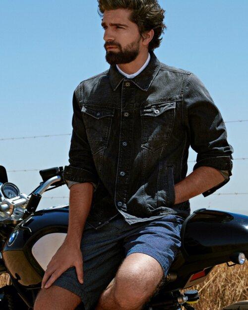Man zittend op een motor in korte broek en donker spijkerjas