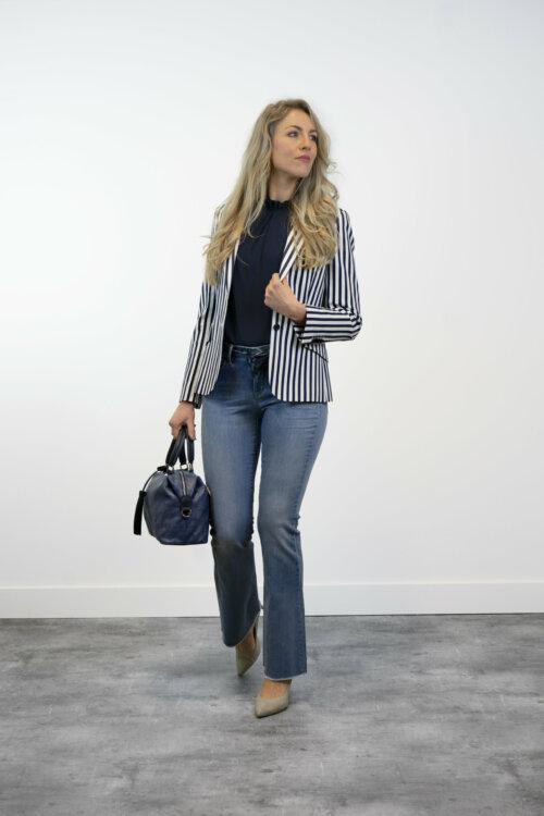 Vrouw in shootruimte met blauwe top, donkerblauw-wit gestreepte blazer en flared jeans