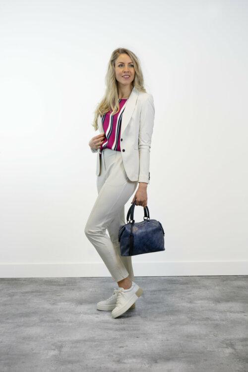 Vrouw in shootruimte met fuchsia-blauw gestreepte top, witte pantalon en witte blazer