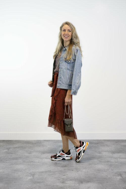 Vrouw in shootruimte met roestkleurige rok en spijkerjack