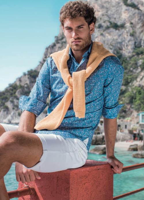 Man die op een leuning zit aan een meer met een donkerblauw Cavallaro overhemd met Paisley patroon en een oranje pullover omgeknoopt