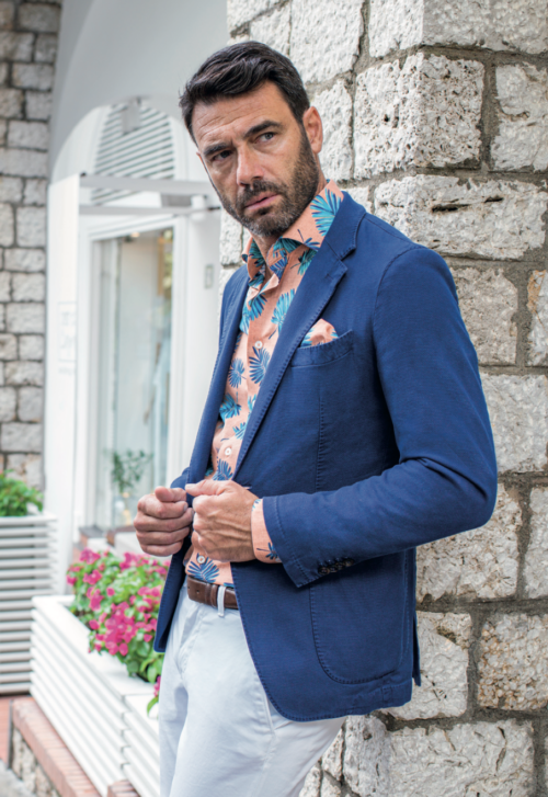 Man die tegen een muur aanleunt met perzikgekleurd Cavallaro overhemd met blauwe veren en donkerblauw colbert