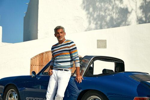 Man die tegen een blauwe cabrio aanleunt met gestreepte State of Art trui en witte jeans
