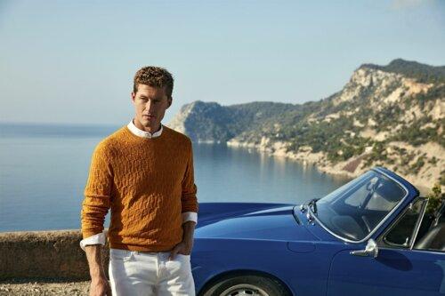 Man die bij een blauwe cabrio staat met uitzicht op een meer in een okergele State of Art pullover met wit overhemd eronder en lichte jeans