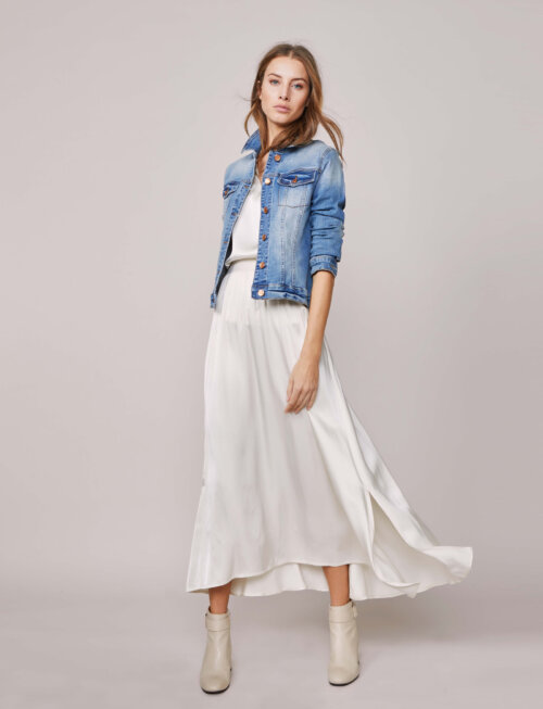 Vrouw staand in studio met spijkerjasje en witte musthaves: rok en top