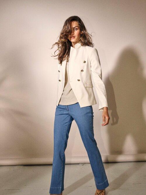 Vrouw staand in studio met witte musthaves: colbert en flared jeans