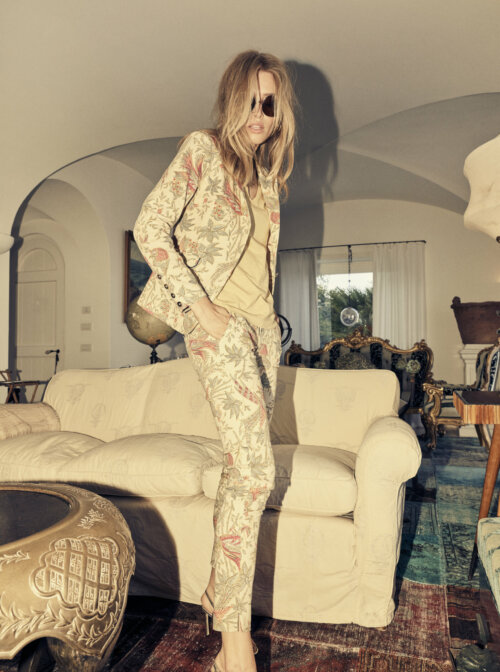 Vrouw in een woonkamer met een gebloemd pak aan