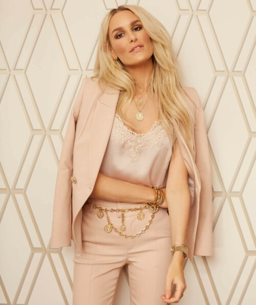 Vrouw tegen een muur aan met een lichtroze gekleurde pak aan, een roze kanten top eronder en een gouden riem om