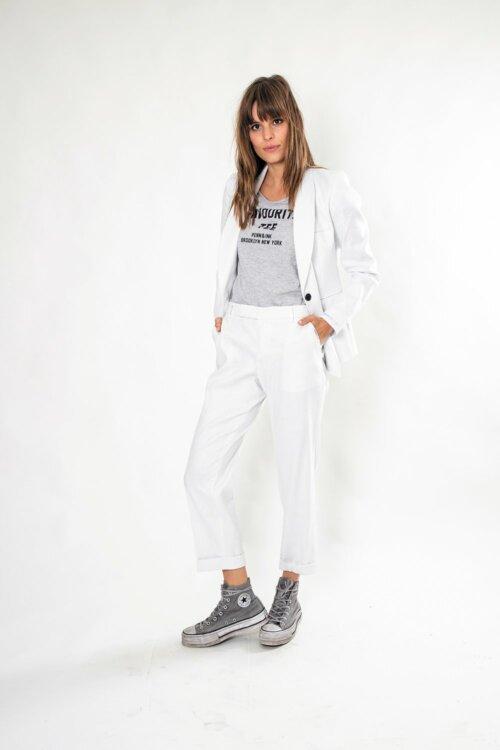 Vrouw in een witte studio met een wit pak met een T-shirt eronder en afgetrapte sneakers eronder