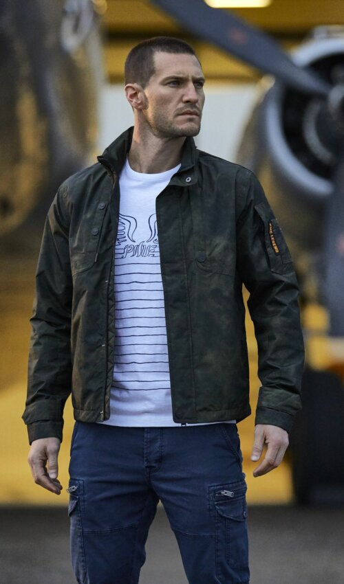 Man staand achter een motor van een vliegtuig in een stoere legerprint gekleurde jas met een wit T-shirt eronder.