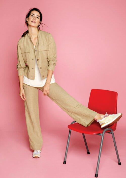 Vrouw in roze shoot ruimte met een voet geleund op een rode stoel, gekleed in beige jasje en beige broek