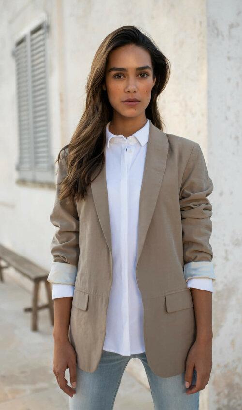 Vrouw die buiten voor een muur staat met een witte blouse en een beige gekleurde blazer aan