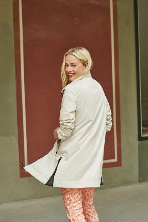 Vrouw voor een muur met beige gekleurde voorjaarsjas aan en kijkend naar achteren
