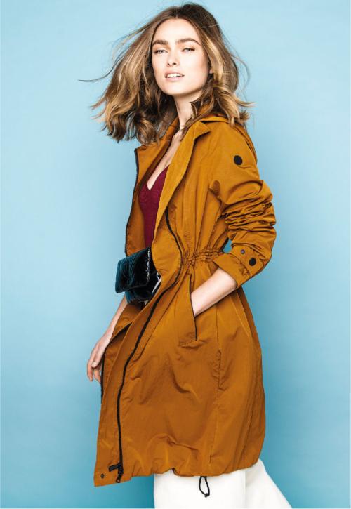 Vrouw in blauwe shoot ruimte met cognac kleurige voorjaarsjas aan