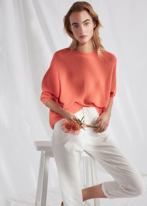 Vrouw zittend op een witte kruk met een oranje Opus trui en een witte broek