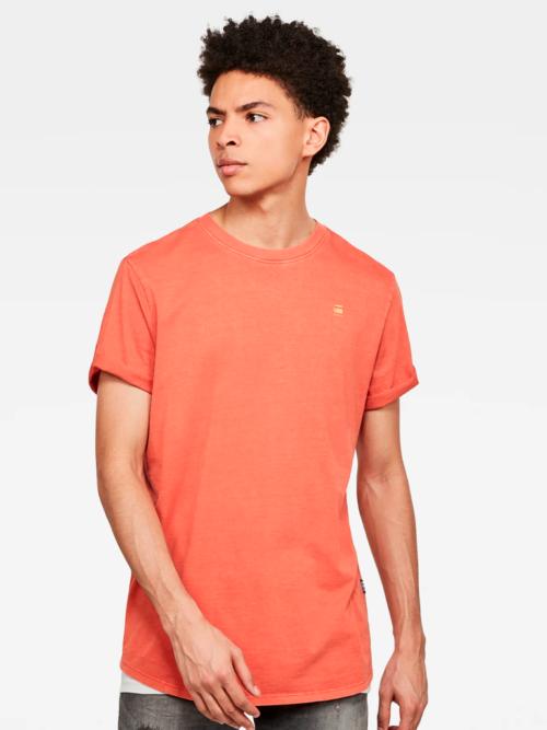 Man in een witte studio in een oranje T-shirt van G-star