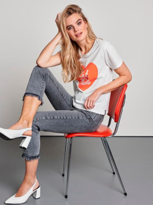 Vrouw zittend op rode stoel in een wit Catwalk Junkie T-shirt met oranje hart