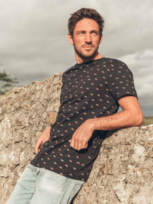 Man leunend tegen een muur in een zwart Kultivate shirt met all over print