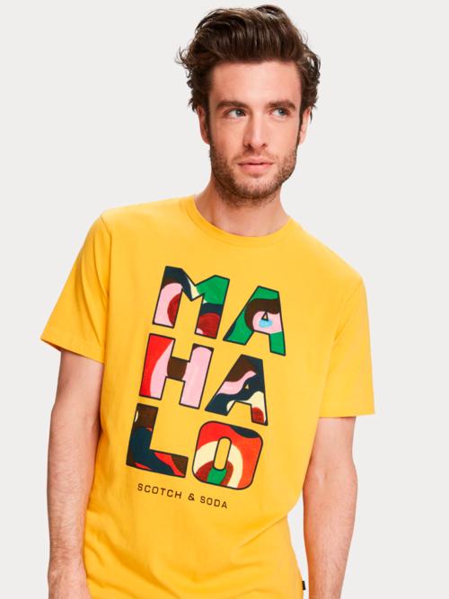 Man in studio met geel Scotch en Soda T-shirt met opdruk tekst