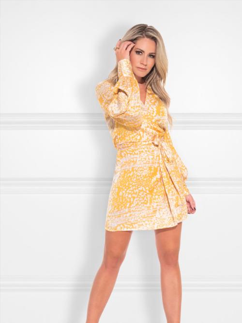 Vrouw in studio met geel Nikkie bloemenprint jurkje