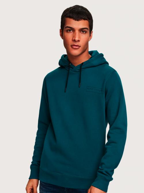 Man met groenblauwe Scotch en Soda hoodie