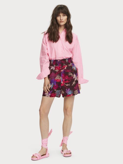 Vrouw in Maison Scotch shorts met roze paarse bladeren print