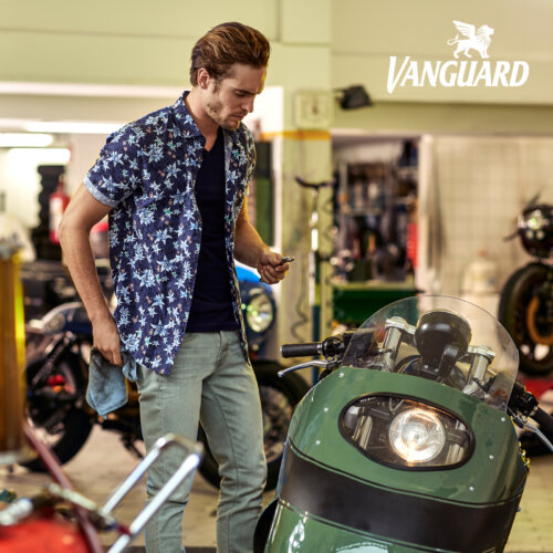 Man in garage met donkerblauw gebloemd korte mouwen overhemd van Vanguard