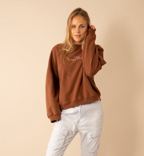 Vrouw in roestkleurige Penn&Ink sweater
